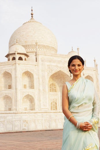 Stock Photo: 1657R-8041 Portrait of a young woman standing in front of a mausoleum, Taj Mahal, Agra, Uttar Pradesh, India