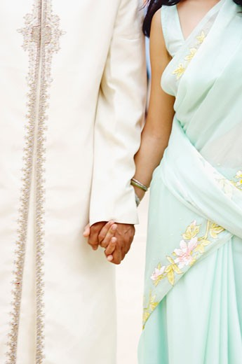Stock Photo: 1657R-8072 Mid section view of a young couple holding hands