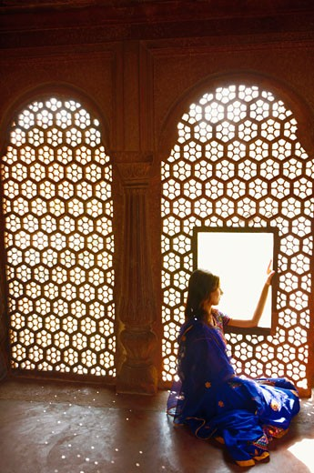 Side profile of a young woman sitting on the floor of a mausoleum, Taj Mahal, Agra, Uttar Pradesh, India : Stock Photo