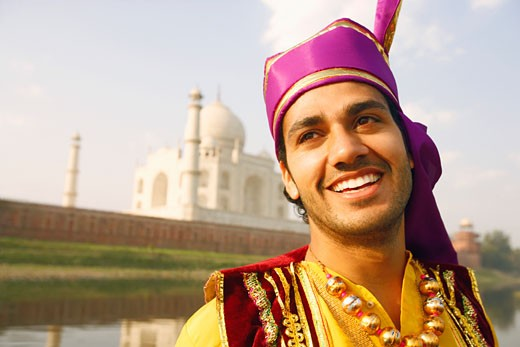 Close-up of a young man smiling in front of a mausoleum, Taj Mahal, Agra, Uttar Pradesh, India : Stock Photo