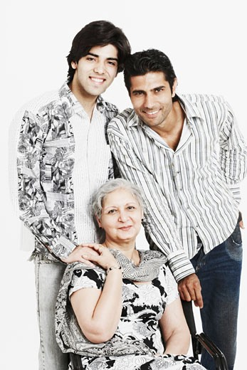 Portrait of two young men standing behind their grandmother : Stock Photo