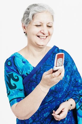 Close-up of a mature woman smiling and looking at a mobile phone : Stock Photo