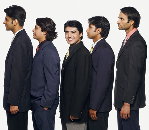 Portrait of a businessman standing in a row with his colleagues : Stock Photo
