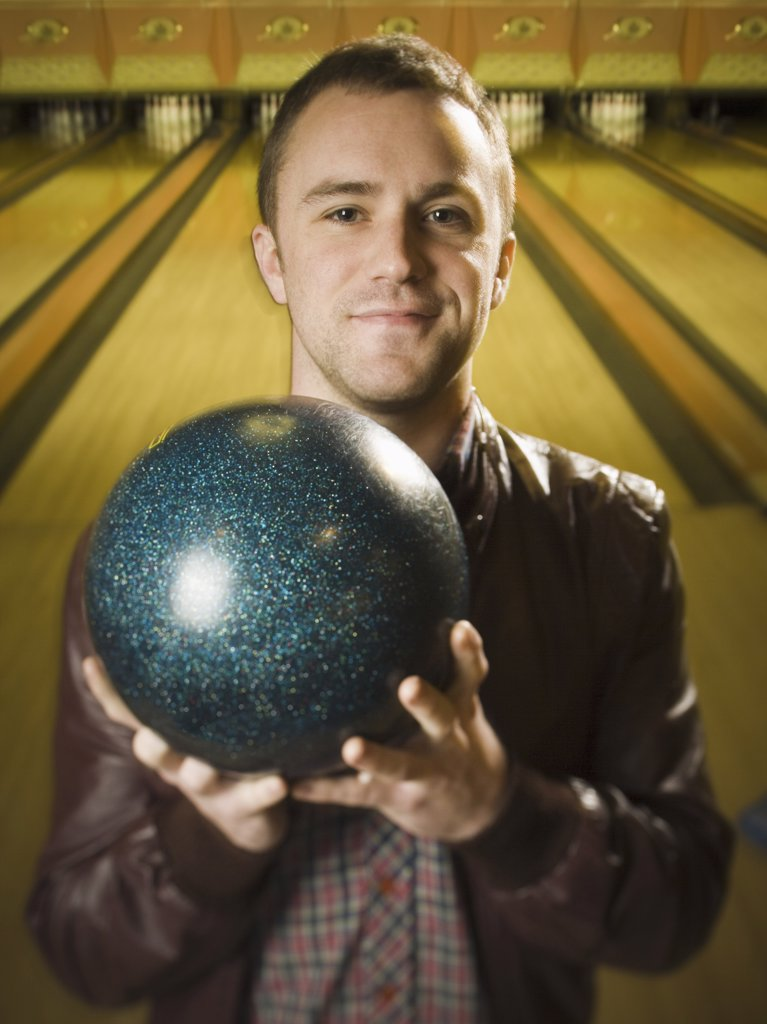 Portrait of a young man holding a bowling ball : Stock Photo