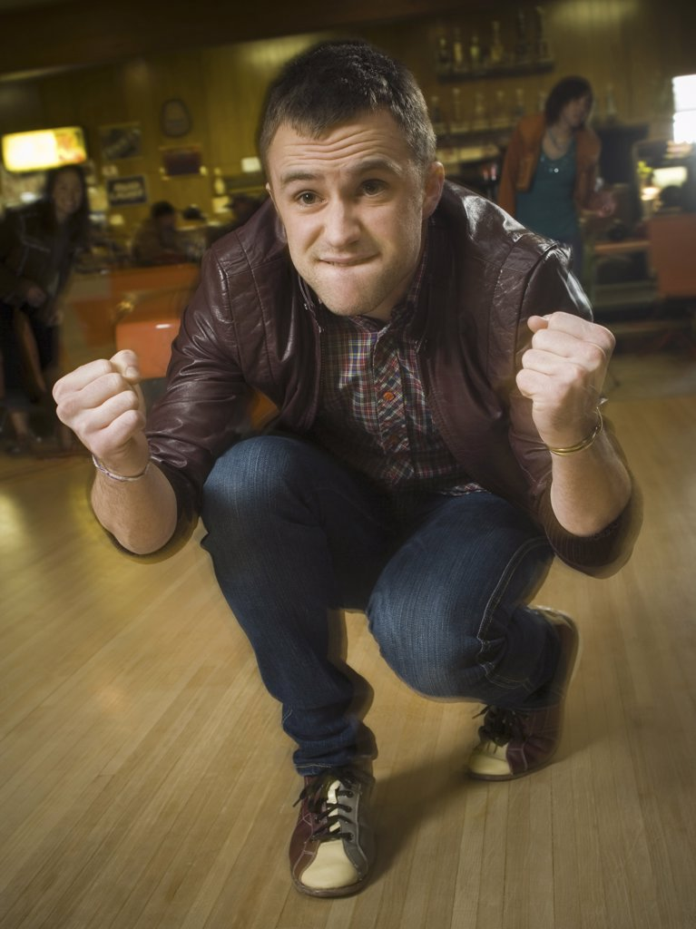 Stock Photo: 1660R-10025 Young man cheering in excitement at a bowling alley