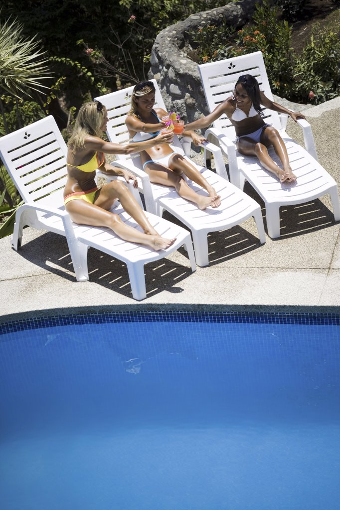 High angle view of three young women by the pool : Stock Photo