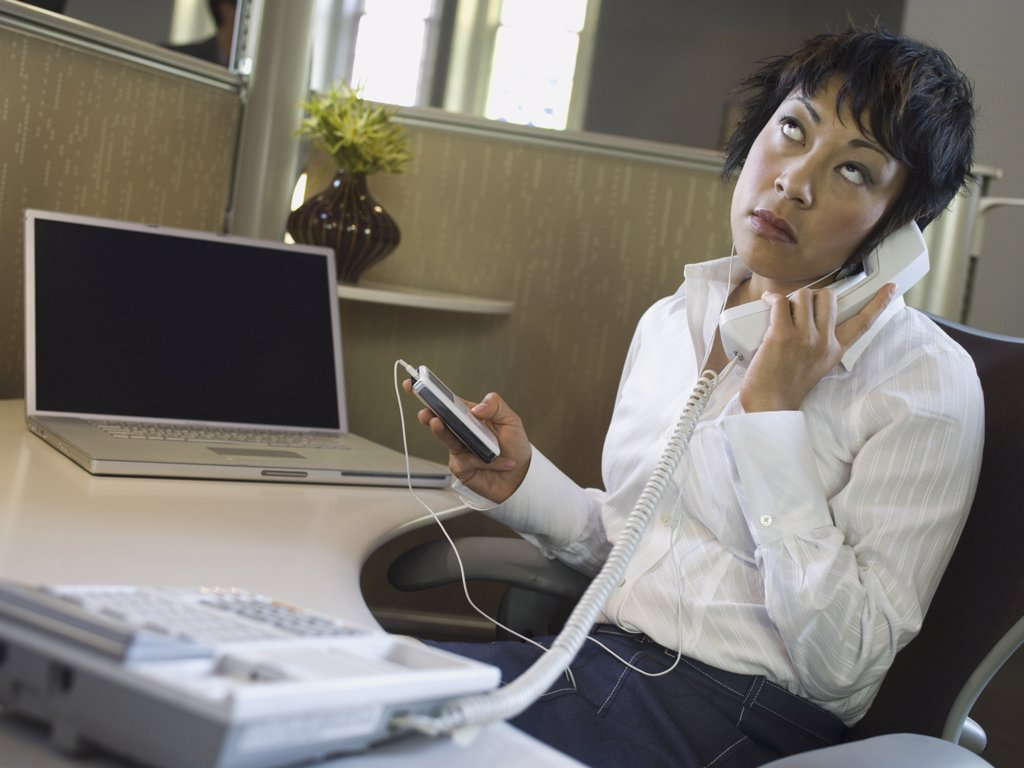 Close-up of a businesswoman with an MP3 player in her hand talking on the telephone : Stock Photo