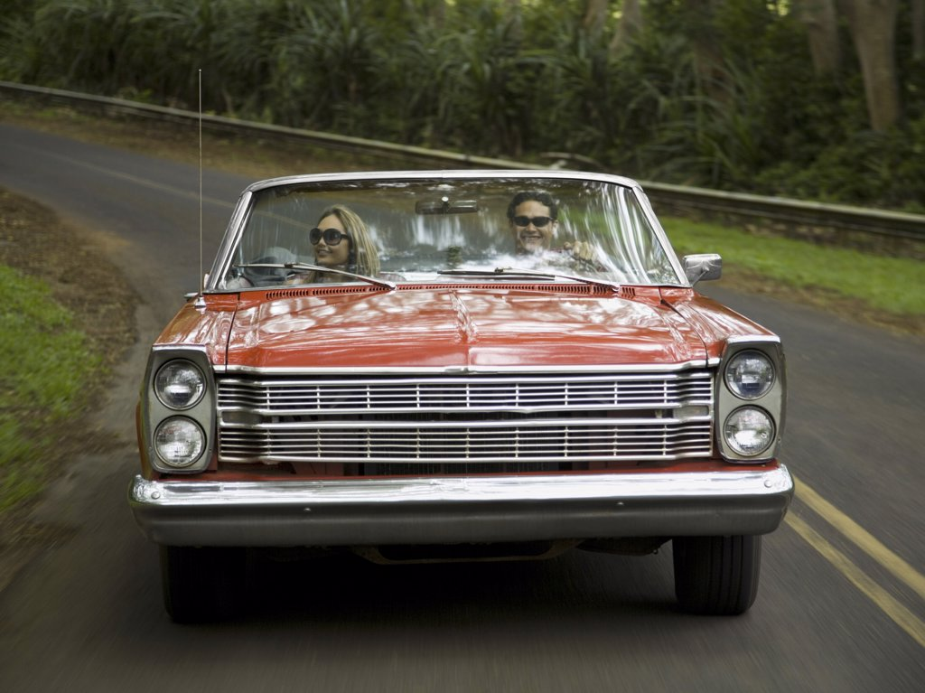 Stock Photo: 1660R-10649 Young couple in a convertible car
