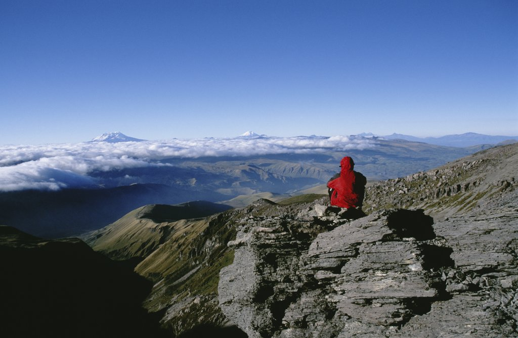 Rear view of a person sitting on a mountain : Stock Photo