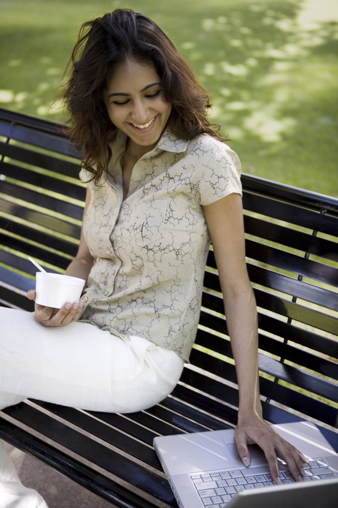 Young woman sitting on a bench using a laptop : Stock Photo