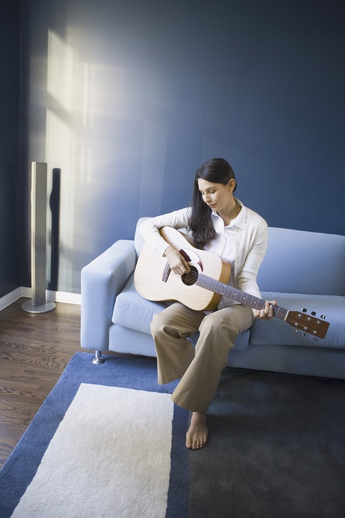 Stock Photo: 1660R-11391 Mid adult woman playing the guitar