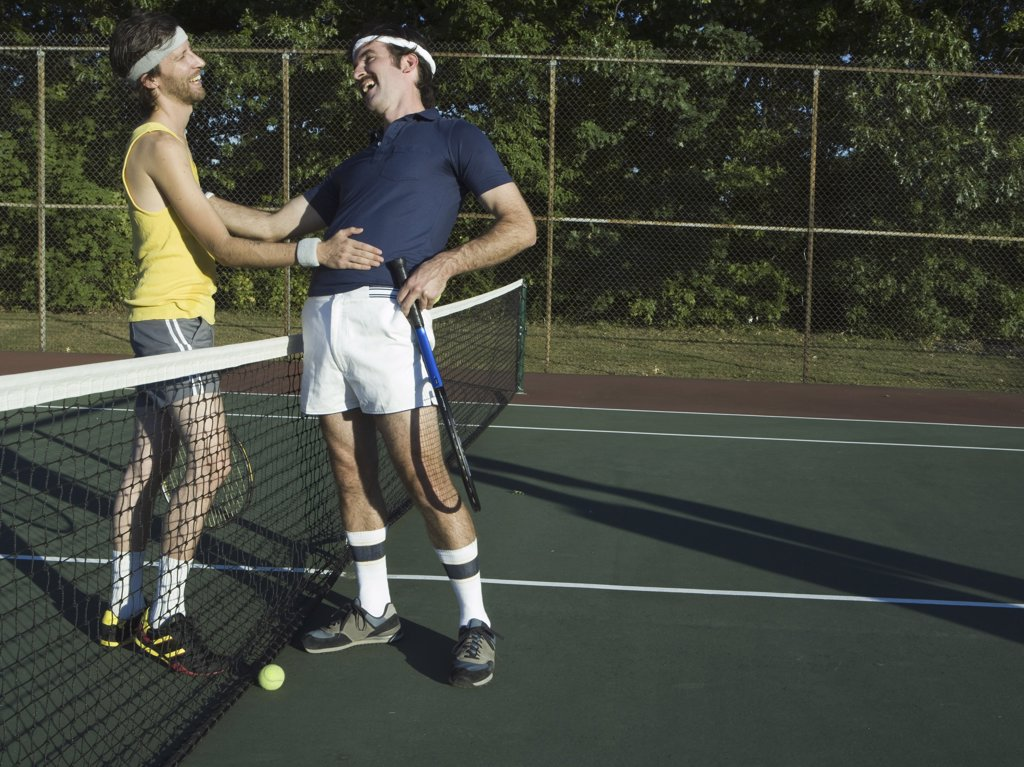 Two young men laughing in a tennis court : Stock Photo