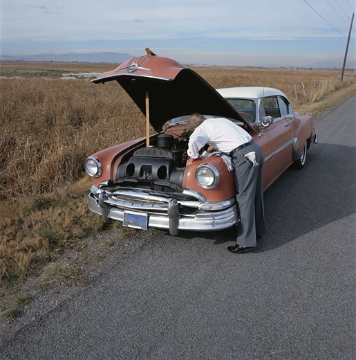 Stock Photo: 1660R-11711 Rear view of a man repairing a vintage car
