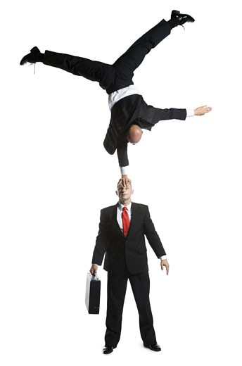 High angle view of two male acrobats in business suits performing : Stock Photo