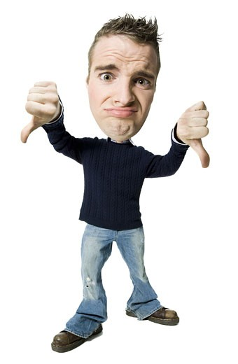 Portrait of a young man showing a thumbs down sign : Stock Photo
