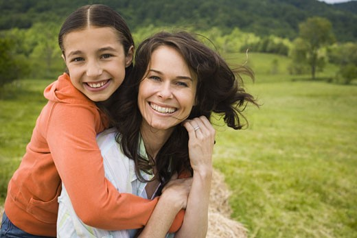 Stock Photo: 1660R-11870 Portrait of a girl hugging her mother from behind