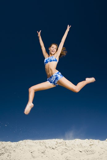 Stock Photo: 1660R-11875 A young woman jumping at the beach