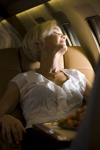 A senior woman sleeping in an airplane : Stock Photo