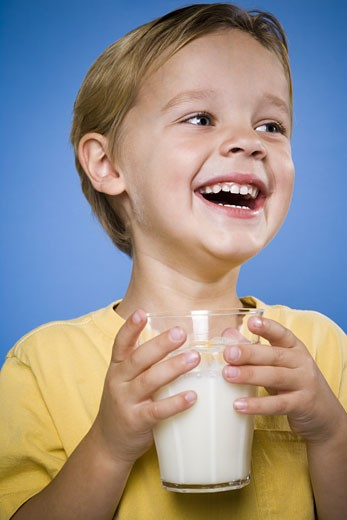 Boy with glass of milk laughing : Stock Photo