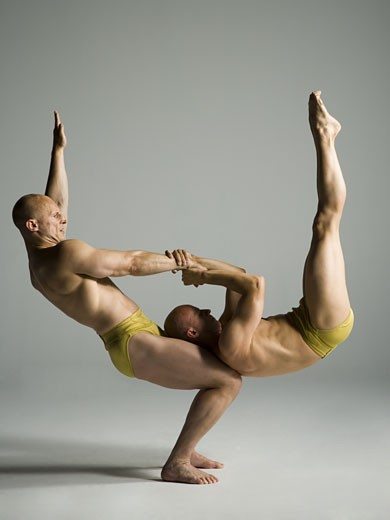 Stock Photo: 1660R-12154 Profile of two male acrobats performing