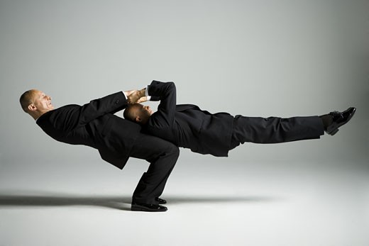 Stock Photo: 1660R-12158 Profile of two male acrobats in business suits performing