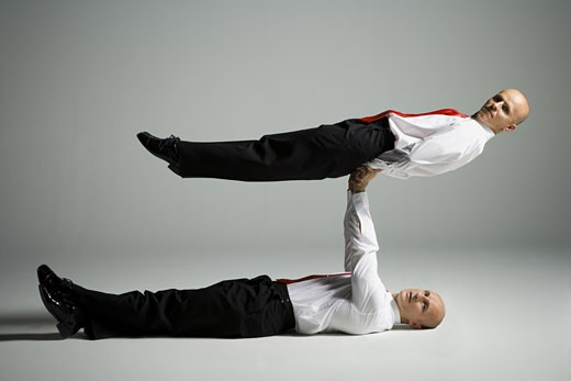 Stock Photo: 1660R-12159 Profile of two male acrobats in business suits performing
