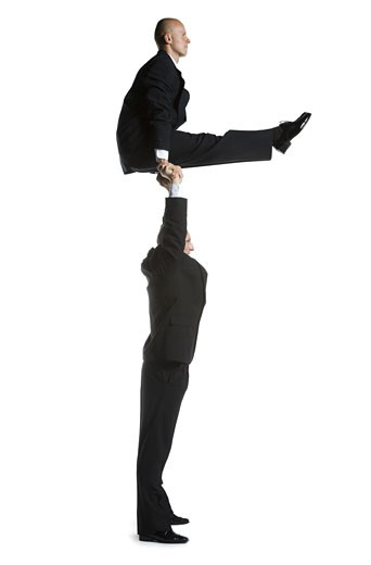 Profile of two male acrobats in business suits performing : Stock Photo