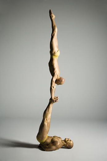 Stock Photo: 1660R-12181 Profile of two male acrobats performing