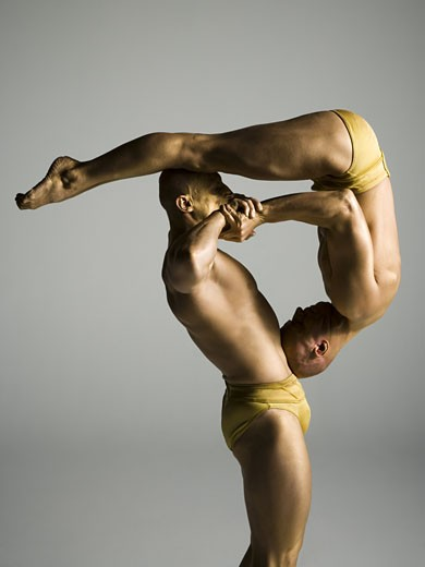 Stock Photo: 1660R-12184 Profile of two male acrobats performing