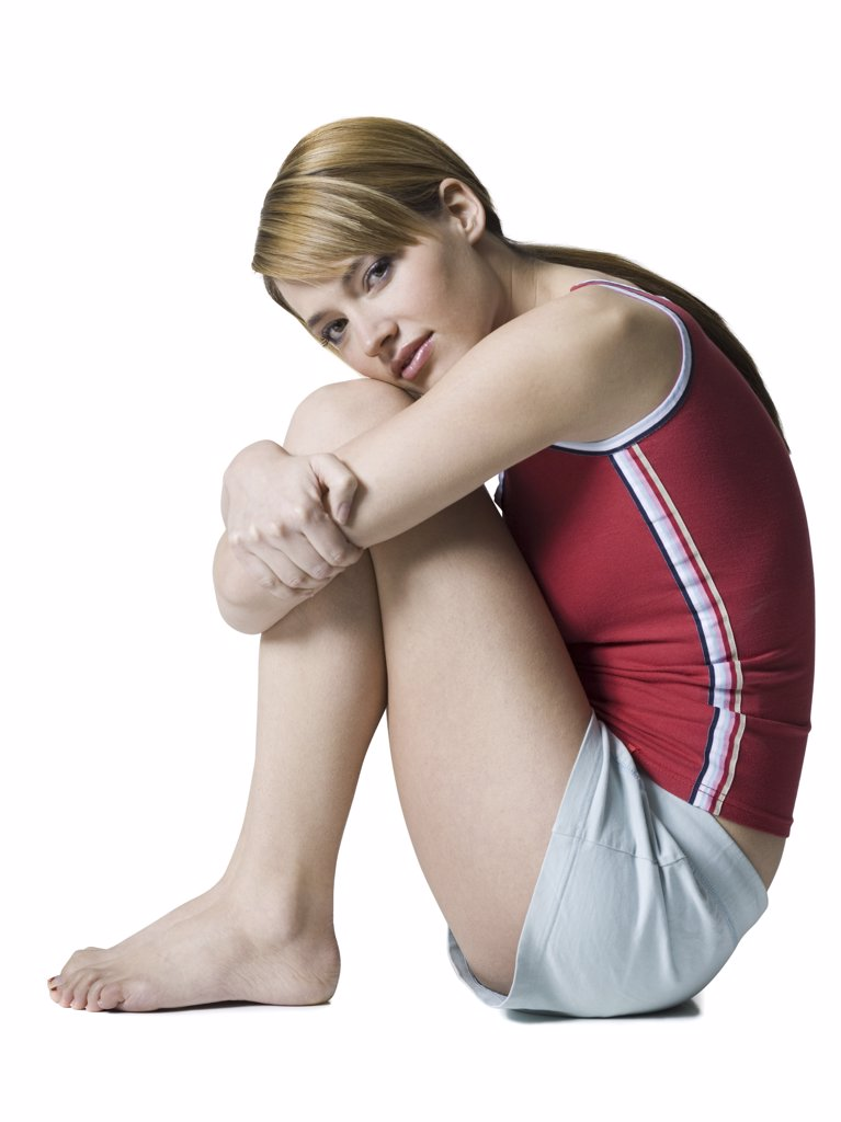 Portrait of a young woman hugging her knees : Stock Photo