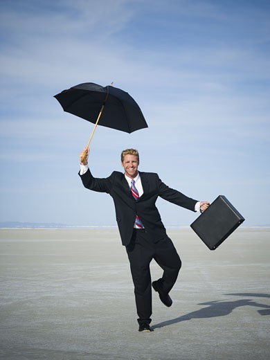 Stock Photo: 1660R-12205 Portrait of a businessman smiling and holding an umbrella