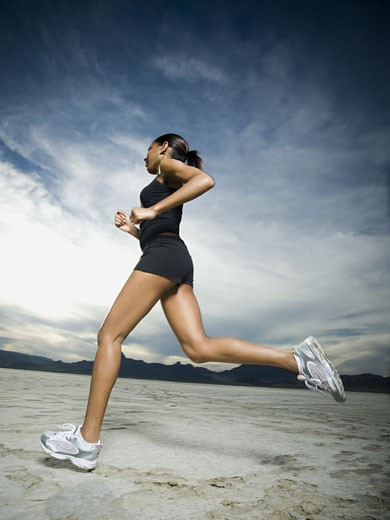 Low angle view of a young woman jogging : Stock Photo