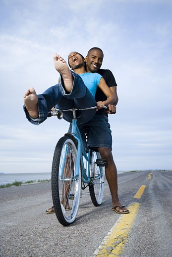 Low angle view of a young couple sitting on a bicycle : Stock Photo