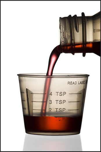 Syrup being poured into a plastic measuring cup : Stock Photo