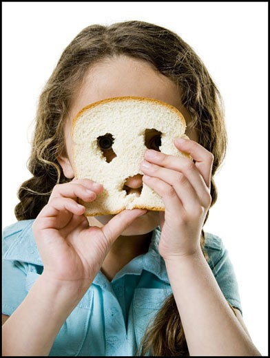 Portrait of a girl looking through a slice of bread : Stock Photo