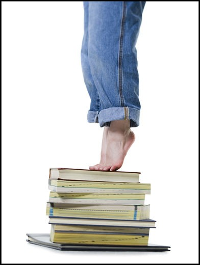 Stock Photo: 1660R-12340 Low section view of a girl standing on a stack of books