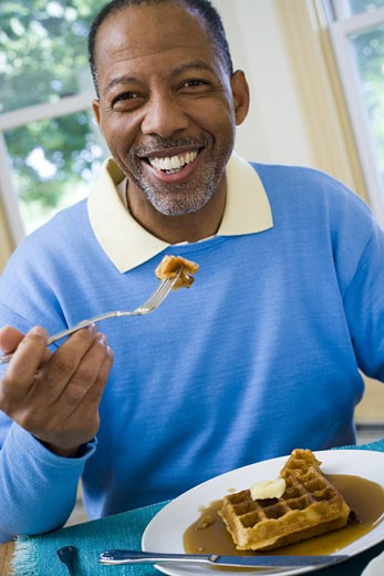 Portrait of a senior man having breakfast : Stock Photo