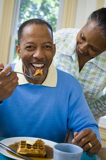 Close-up of a senior man having breakfast with a senior woman behind him : Stock Photo