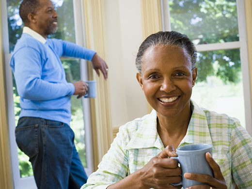 Stock Photo: 1660R-12395 Close-up of a senior woman holding a cup of coffee with a senior man standing behind her