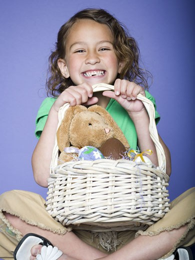 Stock Photo: 1660R-12453 Portrait of a girl holding Easter eggs in a wicker basket