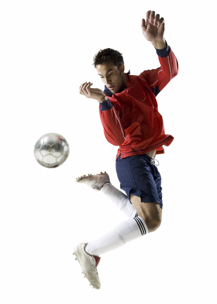 Stock Photo: 1660R-1248 Young man kicking a soccer ball