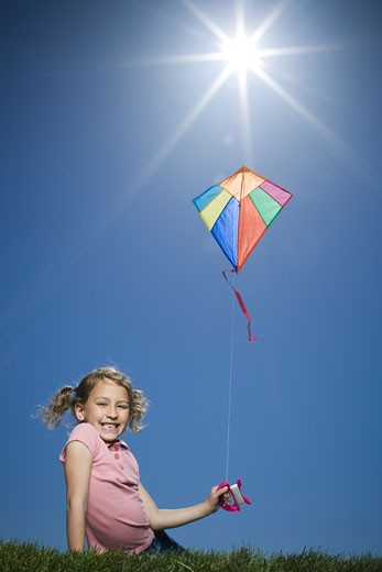 Portrait of a girl flying a kite : Stock Photo