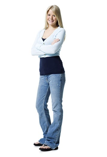 Portrait of a young woman standing with her arms crossed : Stock Photo