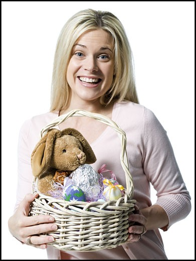 Portrait of a young woman holding a teddy bear in a wicker basket : Stock Photo