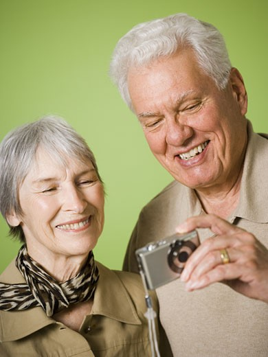 Close-up of an elderly couple looking at a digital camera : Stock Photo