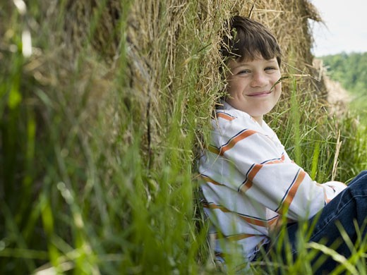Stock Photo: 1660R-12649 Portrait of a boy sitting against a hay bale
