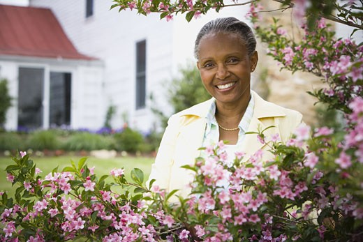 Stock Photo: 1660R-12752 Portrait of a mature woman smiling behind flowers