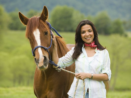Stock Photo: 1660R-12778 Portrait of a woman holding the reins of a horse