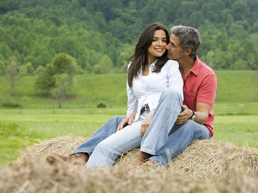 Stock Photo: 1660R-12809 man and a woman sitting on a hay bale