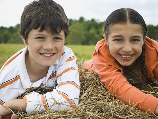Stock Photo: 1660R-12823 Portrait of a boy and a girl lying on top of a haystack